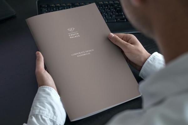 Mann hält den Umschlag des Corporate Design Handbuches des Hotel Cresta Palace in den Händen